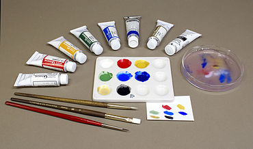 Photo of paints, paintbrushes and palette